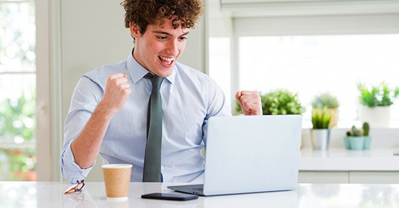 Young business man working with computer laptop at the office screaming proud and celebrating victory and success very excited, cheering emotion
